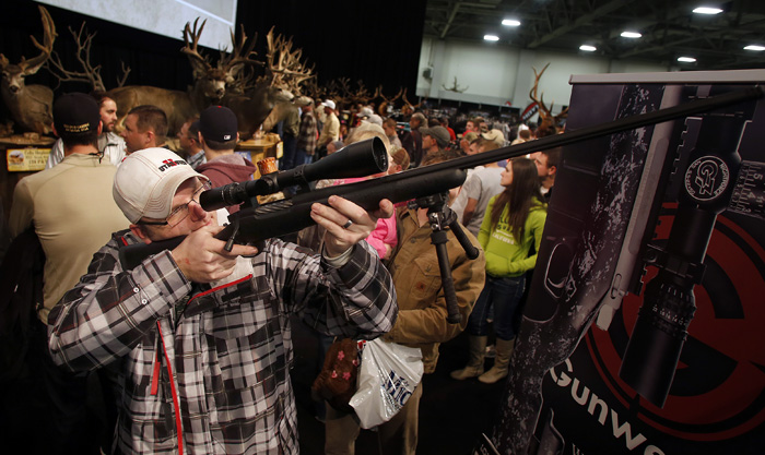 Gun and hunting enthusiast Shawn White holds at a rifle while looking at weapons and equipment at the Western Hunting and Conservation Expo in Salt Lake CIty, Utah, February 23, 2013.  REUTERS/Jim Urquhart  (UNITED STATES)