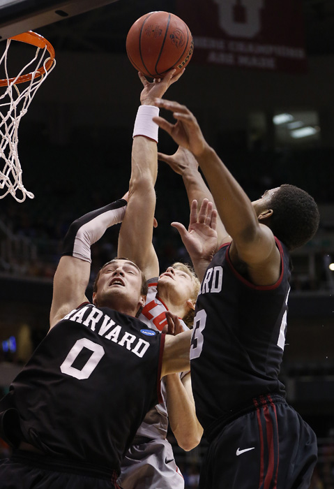New Mexico guard Hugh Greenwood (3) attempts a shot while defended by Harvard guards Laurent Rivard (0) and Wesley Saunders (23) during the first half of their second round NCAA tournament basketball game in Salt Lake City, Utah, March 21, 2013. REUTERS/Jim Urquhart (UNITED STATES)