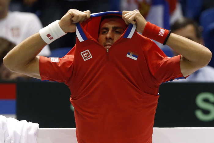 Serbia's Novak Djokovic takes off his shirt during their Davis Cup quarter-final tennis match against United States' John Isner in Boise, Idaho, April 5, 2013. REUTERS/Jim Urquhart (UNITED STATES)