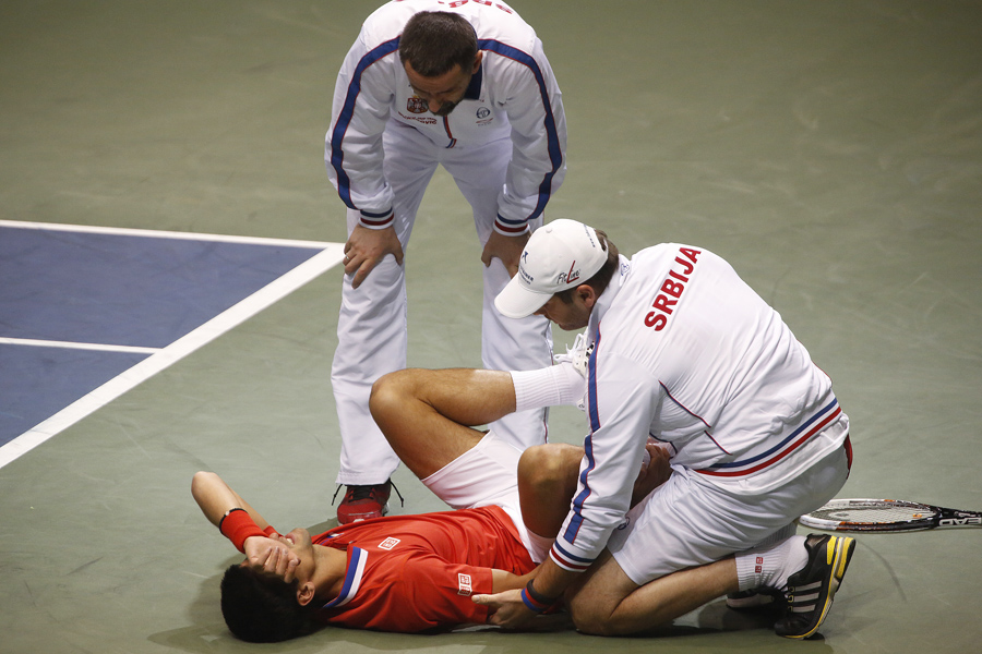 Serbia's Novak Djokovic lays on the court with an injury to his right ankle during his Davis Cup quarter-final tennis match against United States' Sam Querrey in Boise, Idaho, April 7, 2013. REUTERS/Jim Urquhart (UNITED STATES)