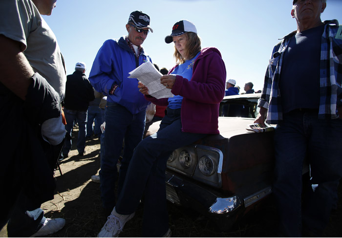 Potential buyers and car enthusiast Rick Fitzler, left, and Gail Meisner monitor the bids as the vintage automobiles from the Lambrecht Collection are put up for auction in Pierce, Nebraska, September 28, 2013. Over 500 classic cars and trucks from an inventory collected by Ray and Mildred Lambrecht will be sold over the weekend. REUTERS/Jim Urquhart  (UNITED STATES)