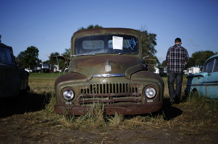 Potential buyers and car enthusiast walk past a International truck that was part of the vintage automobiles from the Lambrecht Collection put up for auction in Pierce, Nebraska, September 28, 2013. Over 500 classic cars and trucks from an inventory collected by Ray and Mildred Lambrecht will be sold over the weekend. REUTERS/Jim Urquhart  (UNITED STATES)