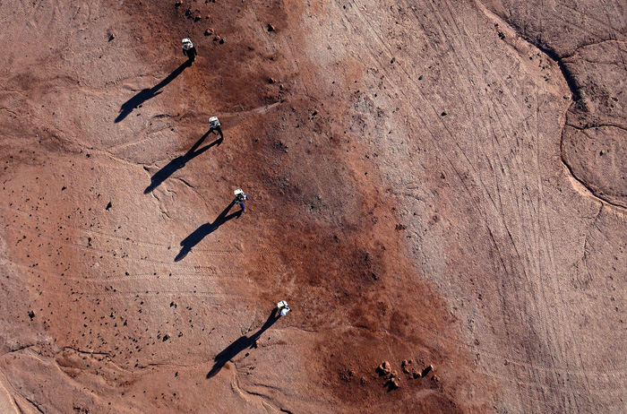 Members of Crew 138 walk across the desert in their simulated space suits at the Mars Desert Research Station in southern Utah. Photo by Jim Urquhart for National Geographic 3/18/2014